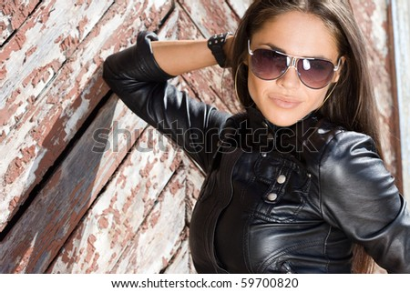 Sexy fashionable woman near the wall - stock photo