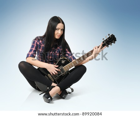 Sexy fashionable young woman with guitar - stock photo