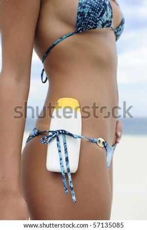 sexy female bikini beach body with  suncream, close-up - stock photo