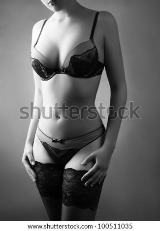 Sexy female body in lingerie on dark background - stock photo