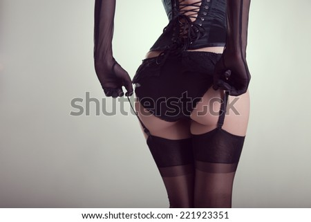 Sexy female buttocks in burlesque lingerie, studio shot on white background   - stock photo
