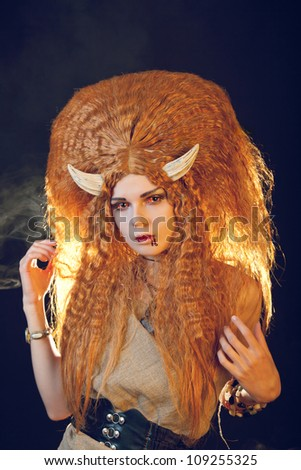 Sexy female demon with bloody lips and curly red hair - stock photo