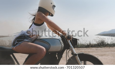 Sexy Female In Protective Helmet Riding Fast On Her Custom Built Cafe Racer Motorcycle The