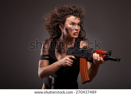 Sexy female killer with AK-74 (Kalashnikov) assault rifle in studio. With dirty face, blood and wound. - stock photo
