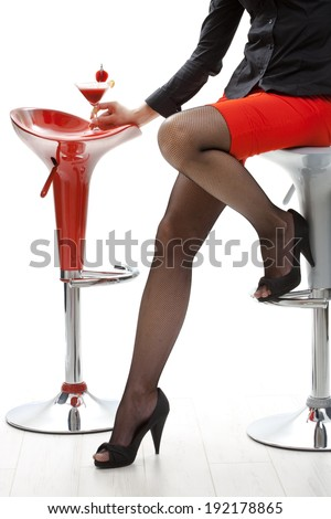 Sexy female legs in black high heels and fishnet stockings, red mini skirt. Holding cocktail drink in bar. White background, sitting on bar stool, close up.  - stock photo