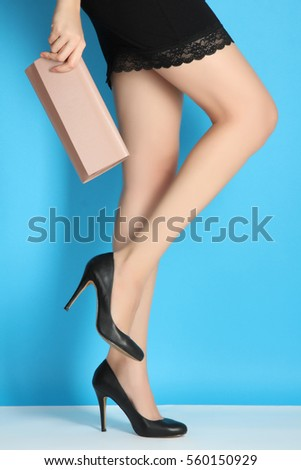 Sexy female legs in high-heeled black female with beige handbag on a blue background.