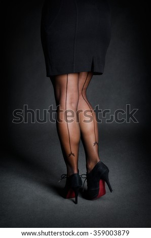 Sexy female legs in skirt and stilettos - stock photo