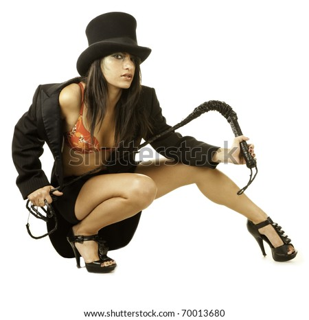 Sexy female lion tamer in circus top hat crouching - stock photo