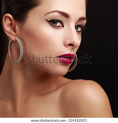 Sexy female model face. Closeup. Bright makeup. Pink lips and black eyeliner. Black background - stock photo