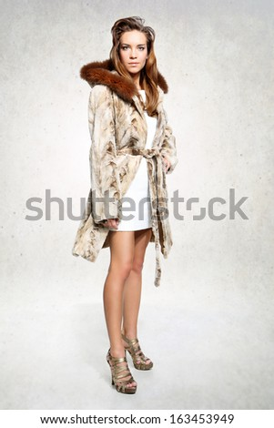 Sexy female model in a luxurious white fur coat  Brunette fashion model in white fur posing on a white background
