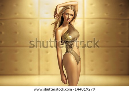 Sexy female model in golden swimsuit - stock photo