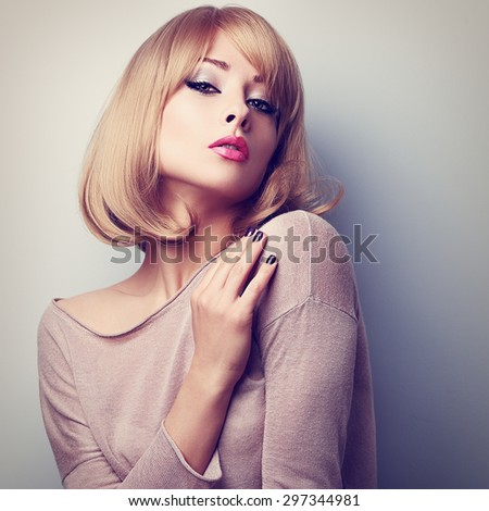 Sexy female model posing with blond short hair style. Color toned closeup portrait - stock photo