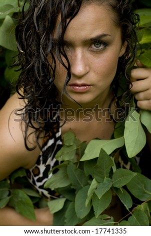 Sexy female model posing with wet hair with leaves around her