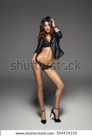 Sexy female model wearing lingerie and leather jacket - stock photo