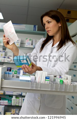 Sexy female pharmacist standing in front of medicine looking prescription - stock photo