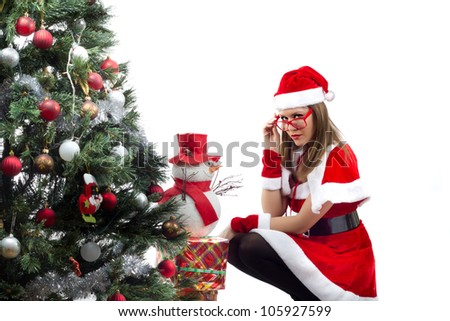 Sexy Female Santa - Young woman dressed in red Mrs. Santa costume posing beside a big Christmas tree, shot on white background - stock photo