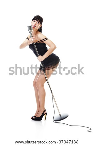 Sexy female singer wearing black dress holding a retro microphone isolated on white