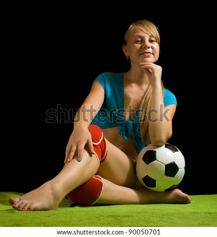 Sexy female soccer player with ball on green against black - stock photo