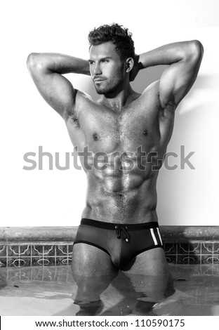 Sexy fine art black and white portrait of a very muscular male model  in swimsuit - stock photo