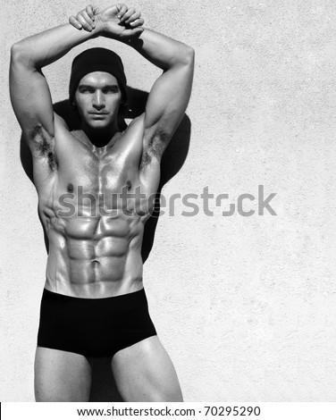 Sexy fine art black and white portrait of a very muscular shirtless male model posing with arms up - stock photo