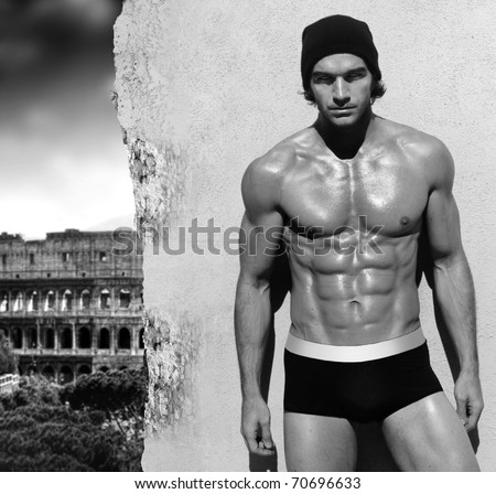 Sexy fine art black and white portrait of a very muscular shirtless male model posing with view of Rome in the background - stock photo