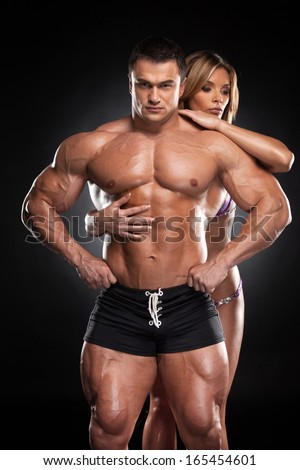 Sexy fit blond girl hugging from behind male bodybuilder. Standing together over black background  - stock photo