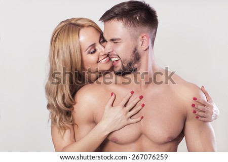 Sexy fit muscled couple in sportswear on neutral grey background hugging - stock photo