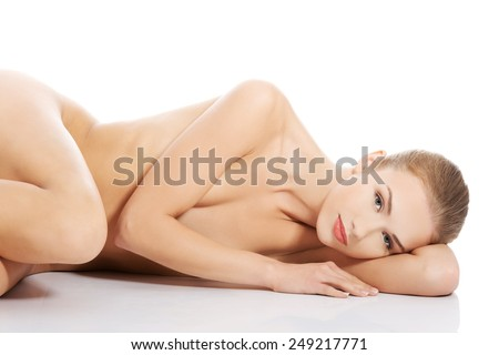 Sexy fit naked woman lying down on the floor - stock photo