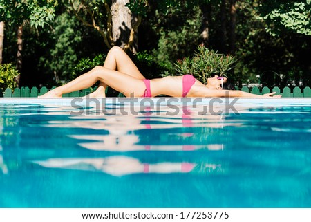 Sexy fit woman sunbathing on summer. Attractive brunette girl relaxing lying down at swimming pool. - stock photo