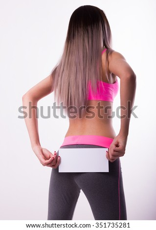 Sexy fitnes brunette in a tracksuit holding empty white board. Girl shows a white board. - stock photo