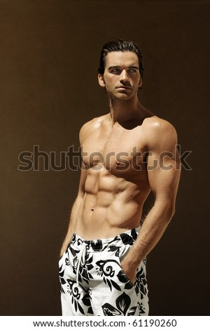Sexy fitness model in swim trunks with copy space - stock photo