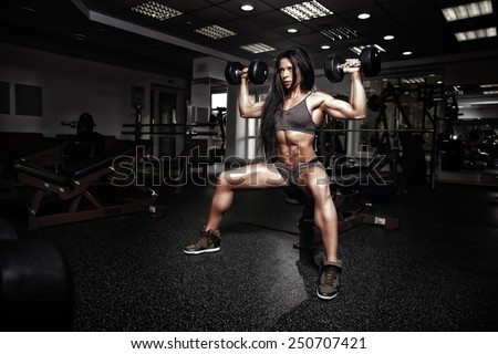 sexy fitness woman in sport wear with perfect fitness body in gym performing shoulder exercises with dumbbell - stock photo