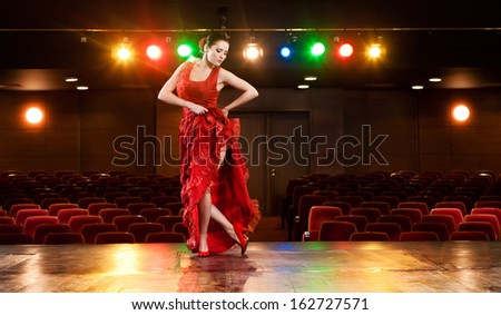 Sexy flamenco dancer performing her dance in a red long dress. - stock photo