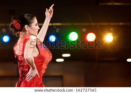 Sexy flamenco dancer performing her dance in a red long dress, arm up.  - stock photo