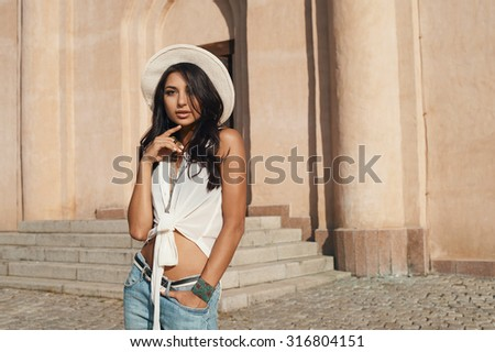 sexy flirting indian lady in jeans, white shirt and white hat against ancient building. She is in harsh morning light. She is positive and playful. Building looks like church or eastern temple - stock photo