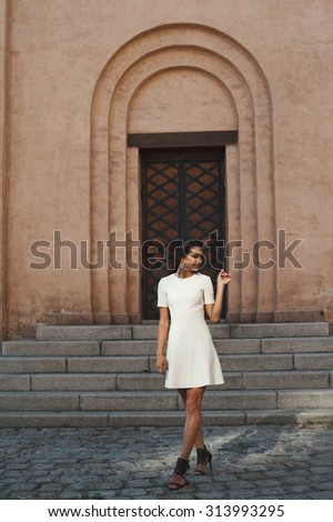 sexy flirting indian lady in white leather dress against ancient building. She standing in shade but lightened by reflected morning sunlight. Light falls down on stairs and paving stones of sidewalk - stock photo