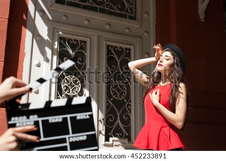 Sexy girl behind a Clapper board. Film-making or film production concept , photo set of young model on vintage building background. Red lips, black hat. dramatic game - stock photo