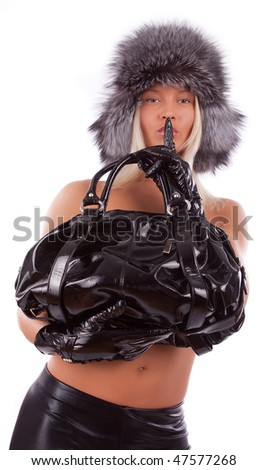 sexy girl holding leather  bag and showing hush sign - stock photo