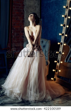 Sexy girl in a luxurious skirt topless. Slim woman topless. A thin girl with big breasts. Elegant posture. Languid girl. Burning light bulb. Dreaming. Sadness. Loves. Suffers. Instituted. Inspiration. - stock photo