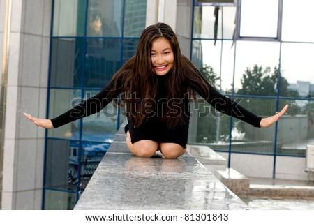 Sexy girl in black dress walking in city - stock photo