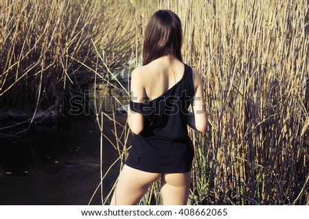 Sexy girl in black t-shirt standing in the reeds - stock photo