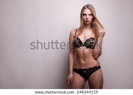 Sexy girl in black underwear on grey studio background. Sexuality and sensuality. Underwear. Model. Studio