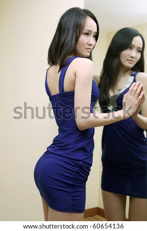 Sexy girl in blue skirt standing beside the mirror,perfect body curve - stock photo