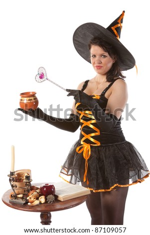 sexy girl in Halloween witch costume prepares a potion - stock photo