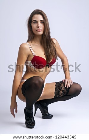 Sexy girl in lingerie posing against a light background