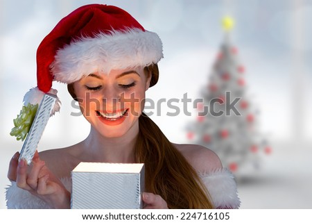 Sexy girl in santa costume opening a gift against blurry christmas tree in room - stock photo