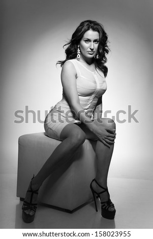 Sexy girl in short dress sitting on cube chair