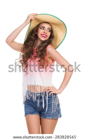 Sexy Girl in Straw Hat. Smiling beautiful young woman in jeans short, pink top and straw hat. Three quarter length studio shot isolated on white. - stock photo