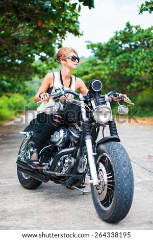 Sexy girl in sunglasses and black jeans posing on a black motorcycle - stock photo