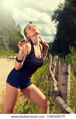 sexy girl in the style of pin-up with e-sigoretoy is on the road in the woods - stock photo